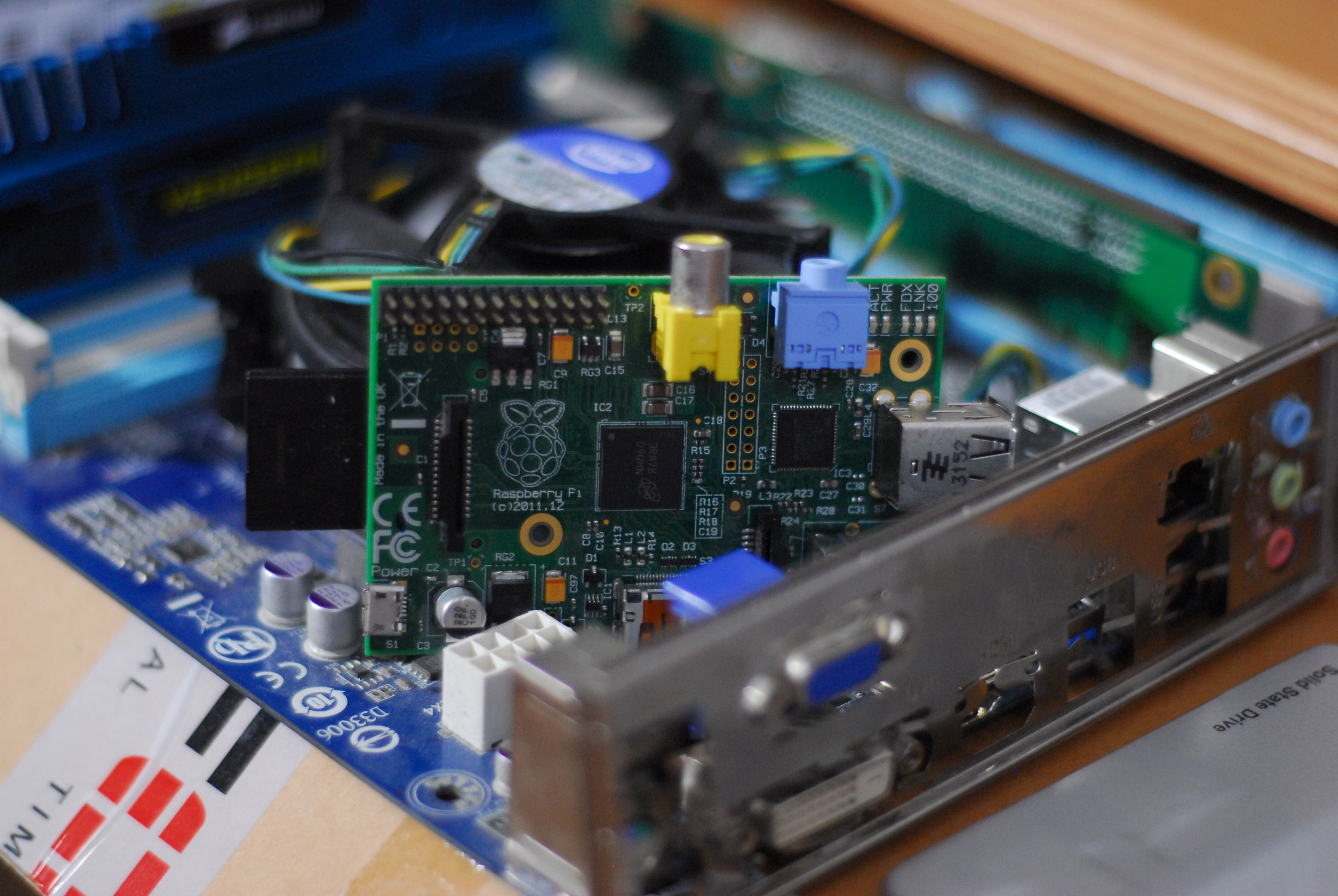 A Raspberry Pi loosely wedged on top of an ATX mainboard